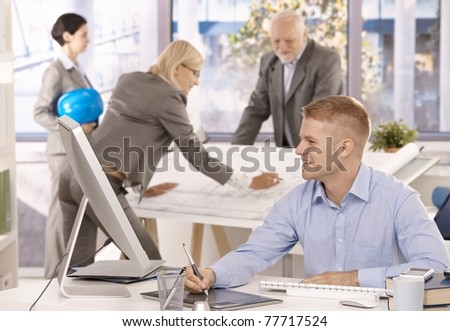 Cheerful architect team working in bright office, smiling.? - stock photo
