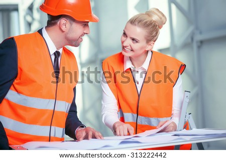 Cheerful architects are standing near a table with blueprint on it. The woman is pointing her finger at sketches. She is explaining her ideas about building to her colleague. They are smiling  - stock photo