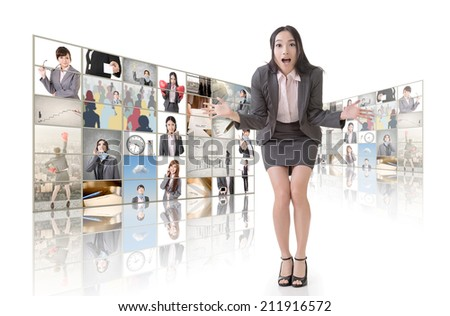 Cheerful Asian business woman standing in front of TV screen wall.