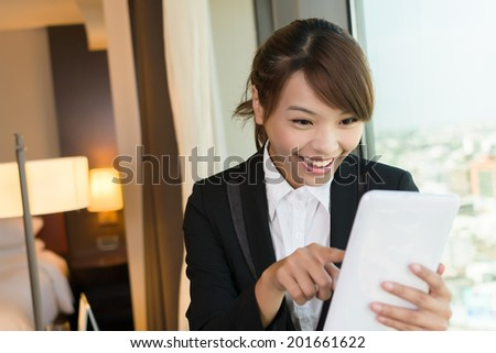 Cheerful Asian business woman using tablet, closeup portrait in hotel room. - stock photo