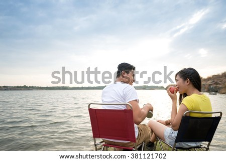 Cheerful Asian campers eating breakfast by the lake