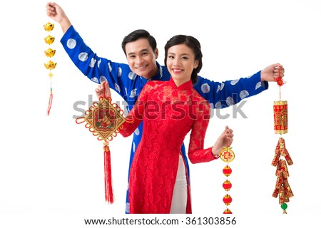 Cheerful Asian couple with various decorations for spring festival - stock photo