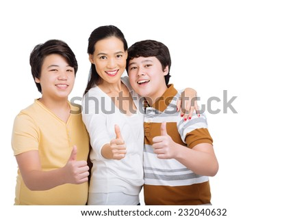 Cheerful Asian family hugging and showing thumbs up - stock photo