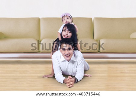 Cheerful Asian family lying on the floor and smiling at the camera, shot at home - stock photo