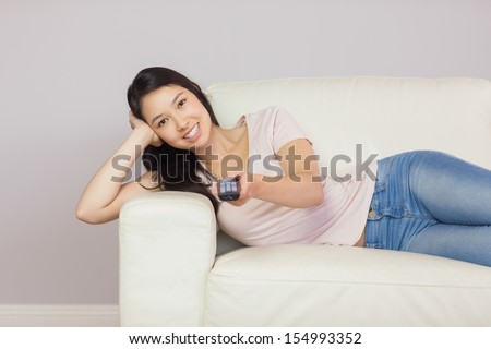 Cheerful asian girl lying on the couch watching tv at home in the sitting room - stock photo