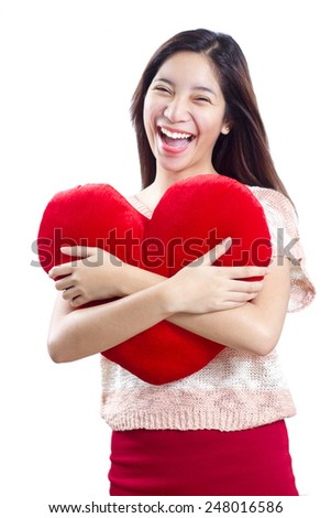 Cheerful  asian lady hugging a red heart shaped pillow. Isolated in white background. - stock photo