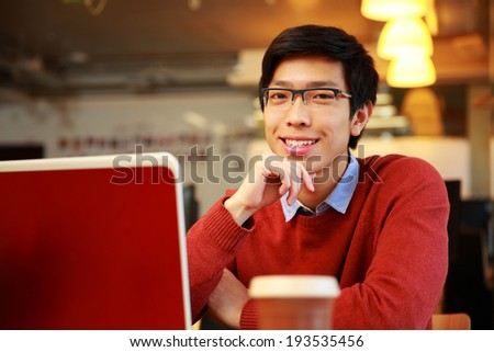 Cheerful asian man sitting at the table with laptop and looking at camera - stock photo