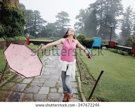 Cheerful Asian student enjoying rain. - stock photo