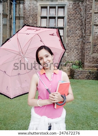 Cheerful Asian student outdoor during rainy season. - stock photo
