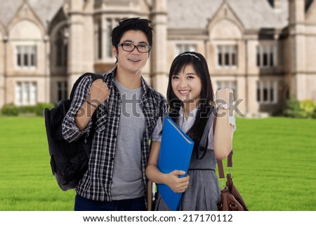 Cheerful asian students celebrate their achievement in front of the school - stock photo