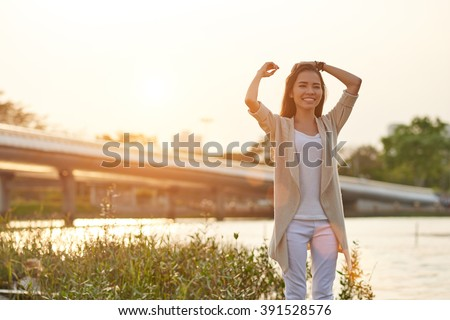 Cheerful Asian woman standing at the river at sunset