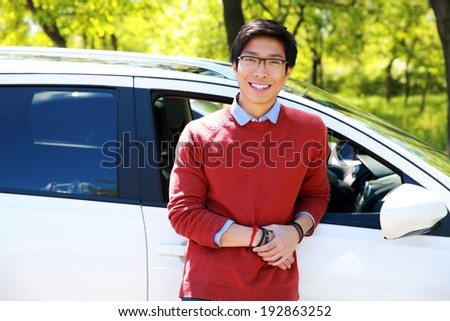 Cheerful asian young man standing near his car in park - stock photo