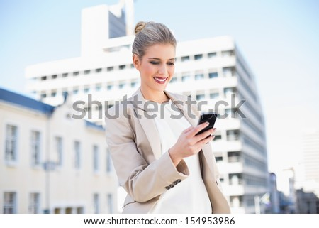 Cheerful attractive businesswoman sending a text message outdoors on urban background - stock photo