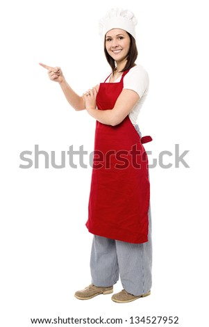 Cheerful attractive female chef pointing towards copy space area.