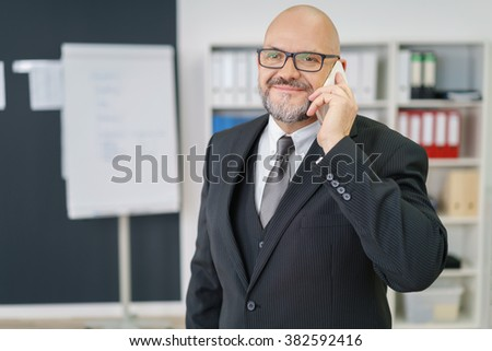 Cheerful attractive mature businessman in suit with bald head, beard and eyeglasses talking on phone in office - stock photo