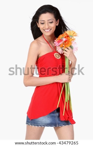 Cheerful attractive teenage girl with orange and pink daisy flowers