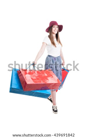 Cheerful attractive woman enjoying shopping to buy clothes and having good time isolated on white studio background - stock photo