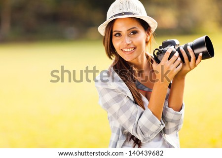 cheerful attractive woman holding a camera outdoors - stock photo