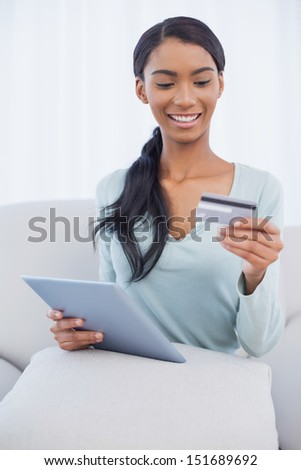 Cheerful attractive woman in bright living room using her tablet pc to buy online