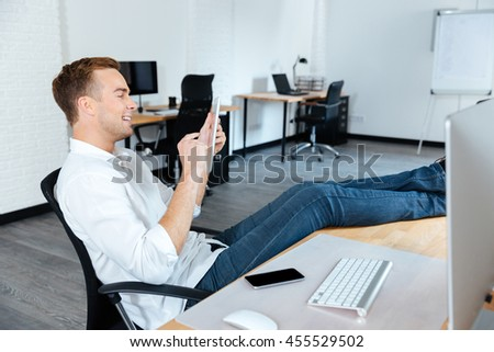 Cheerful attractive young businessman sitting with legs on table and using tablet in office - stock photo
