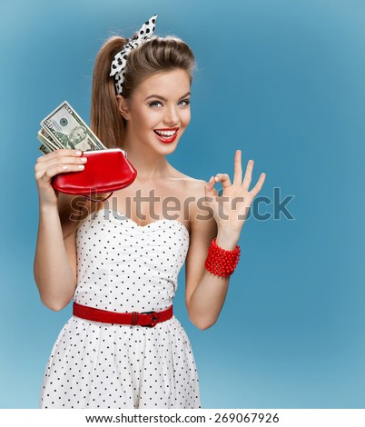 Cheerful attractive young lady holding cash and showing It's Okay. Shopping concept / photo set of young American pin-up model on blue background - stock photo