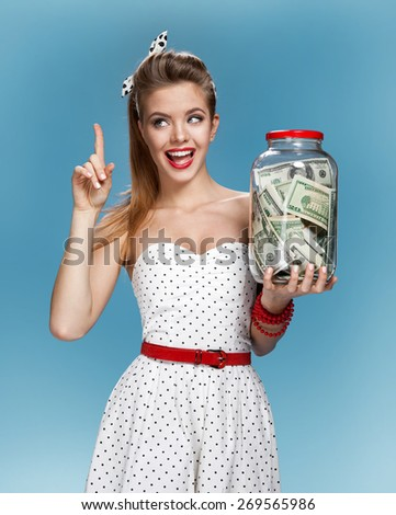 Cheerful attractive young lady holding jar of money and happy smiling. Shopping concept / photo set of young American pin-up model on blue background - stock photo