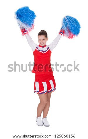 Cheerful attractive young teenage cheerleader in her red - stock photo