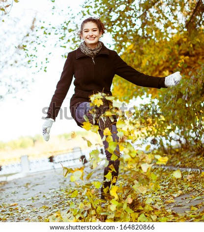 Cheerful attractive young woman in autumn park - stock photo