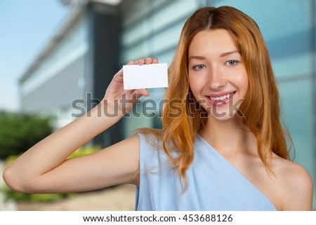 Cheerful attractive young woman showing blank sheet of paper with copy space - stock photo