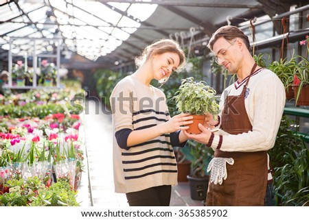 Cheerful attractive young woman with help of handsome man gardener choosing flowers in pot in garden center - stock photo
