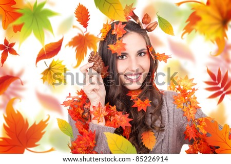 cheerful autumn woman holding cone with leaves in hair