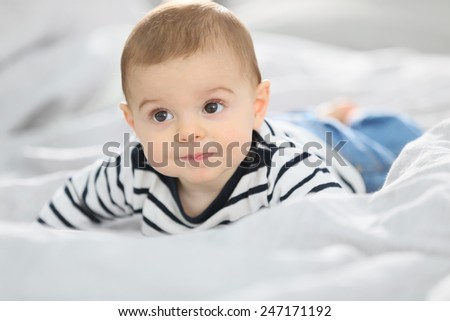 Cheerful baby boy laying over bed - stock photo
