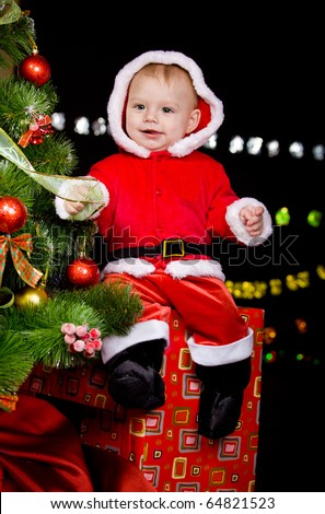 Cheerful baby boy sitting on the present box beside Christmas tree - stock photo