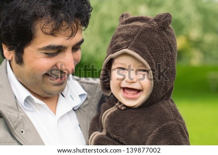 Cheerful baby boy with his father outdoors laughing - stock photo