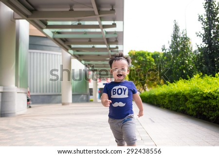 Cheerful baby. Child running outdoor in park. Green tree leaf and sunny day - stock photo