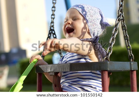 Cheerful baby girl having fun in a swing - stock photo