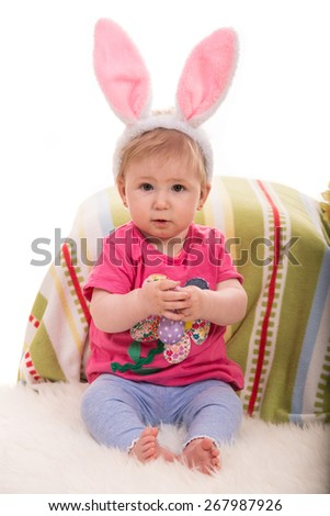 Cheerful baby girl with bunny ears holding lilla Easter egg and sitting on fluffy blanket - stock photo