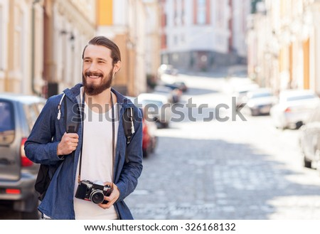 Cheerful bearded male tourist is walking across town. He is looking around and smiling. The guy is holding camera and photographing building. Copy space in right side - stock photo
