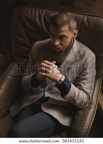 Cheerful bearded man is making serious decision - stock photo