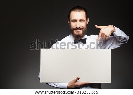 Cheerful bearded man is showing white empty billboard. He is pointing his finger at it and smiling. The man is standing and looking at the camera happily. Isolated and copy space in left side - stock photo
