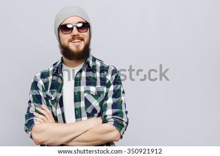 Cheerful bearded man, wearing on white t-shirt, gray hat, sunglasses and blue checked shirt, posing with crossed hands, on white background, in studio, waist up - stock photo