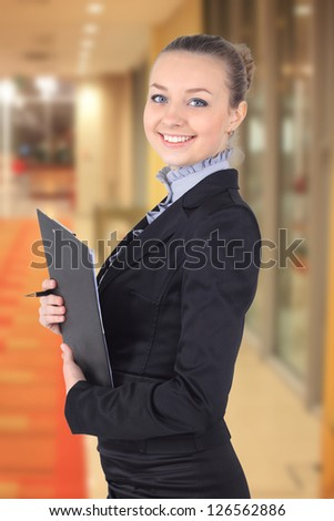 Cheerful beautiful business woman with clipboard writing,