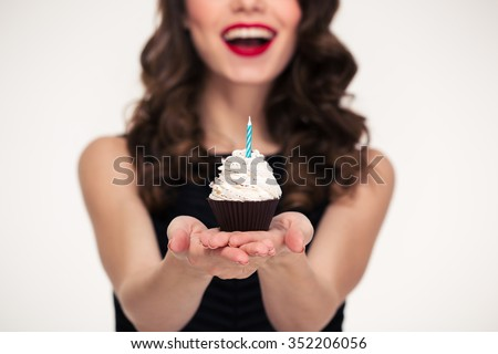 Cheerful beautiful curly young woman in retro style giving birthday cupcake with candle - stock photo