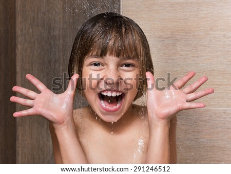 Cheerful beautiful girl bathing under a shower at home - stock photo