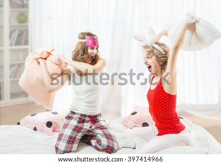 Cheerful beautiful girl friends fighting on the pillows. Active entertainment. Bright room with large windows. Of Sunny interior. Bright emotions Pijamas party cool active mood festive atmosphere
