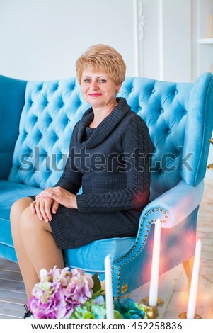 Cheerful beautiful grandmother sitting on luxurious couch blue, against background of cozy room