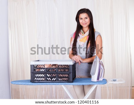 Cheerful beautiful housewife doing the ironing displaying a large container full of clean laundry - stock photo
