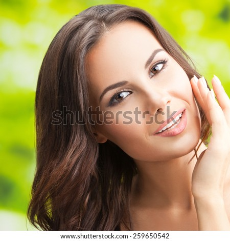 Cheerful beautiful smiling woman touching skin or applying cream, outdoors - stock photo