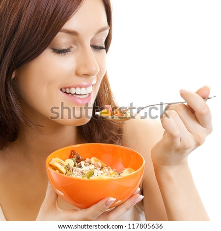 Cheerful beautiful woman eating muslin, isolated over white background - stock photo