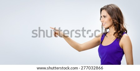Cheerful beautiful woman in violet casual smart clothing, showing copyspace, visual imaginary or something, or pressing virual button, on grey background, with blank area for slogan or product or text - stock photo